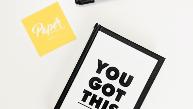 A picture of a tablet showing the statement 'You Got This', a stick note with the word Paper on the left side of the tablet, and an uncapped black Sharpie pen on the top side of the tablet.